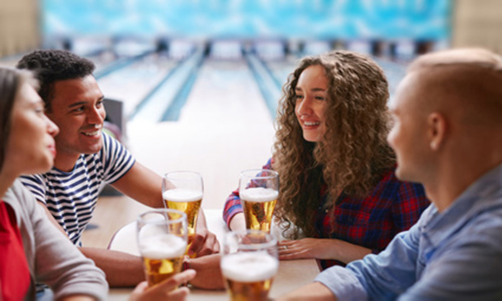 adults bowling with beer